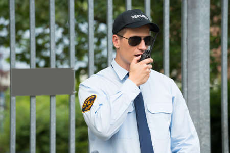 Close-up Of Male Security Guard Talking On Walkie-talkie Stockfoto