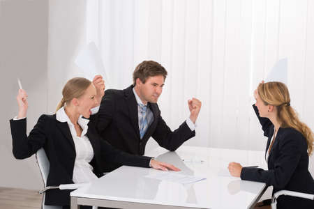 Displeased Young Businesspeople Having Argument At Workplace