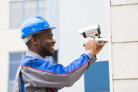 Junger glücklicher männlicher Techniker, der Kamera mit Schraubenzieher repariert Standard-Bild