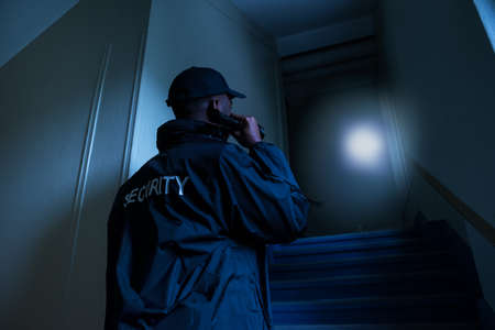 Rear View Of Male Security Guard Holding Flashlight
