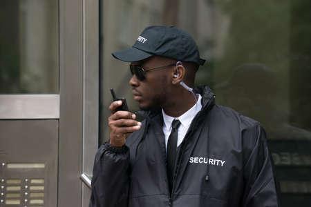 Portrait der jungen afrikanischen Mann Security Guard Gespräch über Walkie-Talkie