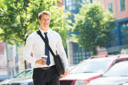 Portrait Of Happy Young Businessman With Disposal Cup Stock Photo
