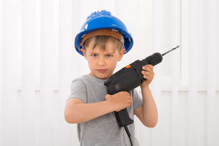 Portrait Of A Boy In Hard Hat Holding Electric Drill
