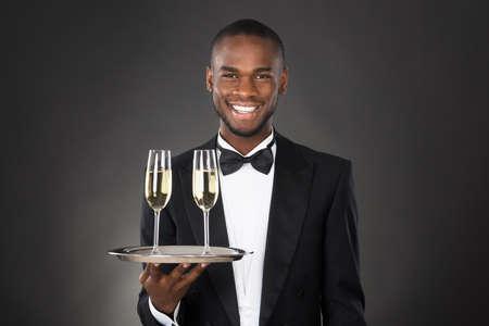 doorkeeper: African Waiter Holding Champagne Drink Against Black Background