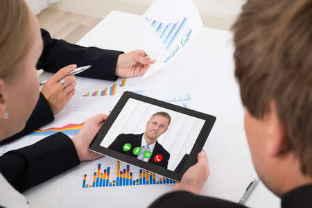 conferencing: Close-up Of Businesspeople Video Conferencing On Digital Tablet In Office