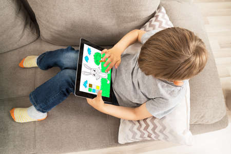 High Angle View Of Boy Sitting On Sofa Enjoying Game On Digital Tablet Stock Photo