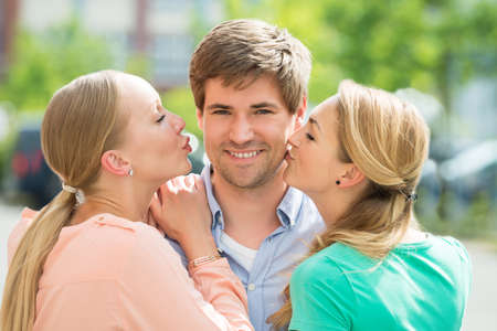 women kissing women: Close-up Of Two Women Kissing Young Handsome Man