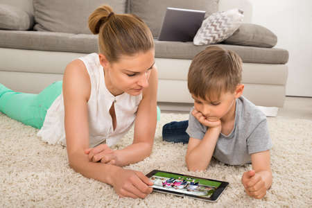 Mother And Son Lying On Carpet Watching Movie On Digital Tablet At Home Stock Photo
