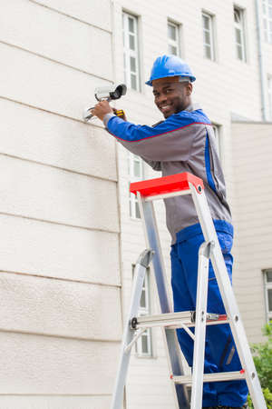 Young Happy Male Technician On Ladder Repairing Surveillance Camera