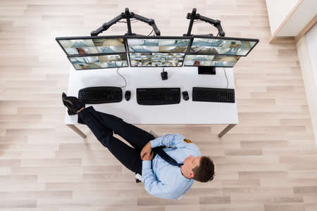 footage: High Angle View Of Security Guard Sleeping In Front Of Multiple Computers Showing CCTV Footage