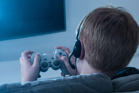 videogame: Close-up Of A Boy Holding Joystick Playing Videogame Stock Photo