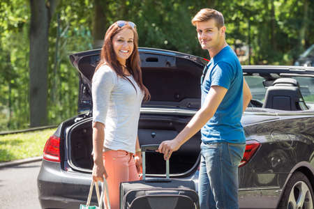 car trunk: Portrait Of Young Happy Couple Putting Luggage In A Car Trunk Stock Photo