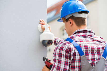 Young Male Technician Installing Camera On Wall Using Electric Cordless Drill Stock Photo