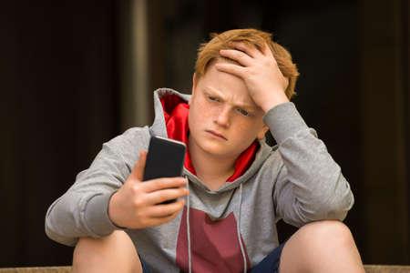 Trauriger Junge auf der Suche Handy mit der Hand auf Kopf