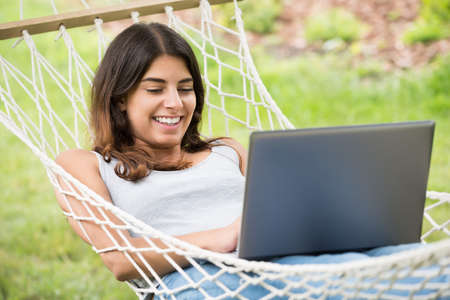 surfing the internet: Smiling Young Woman Lying On Hammock Using Laptop Stock Photo