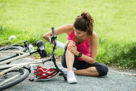 Jonge vrouw met pijn in de knie Bij omlaag gedaald van Bicycle