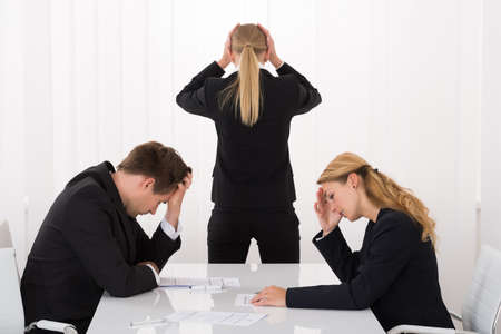 unsatisfactory: Sad Young Businesspeople With Hands On Head In Office