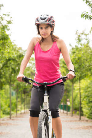 cycling helmet: Young Female Cyclist Riding Her Bicycle With Safety Helmet Stock Photo