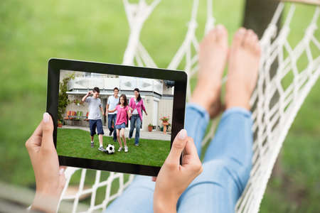 Close-up Of Woman In Hammock Watching Movie On Digital Tablet photo