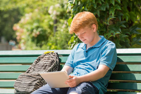 e book device: Schoolboy Sitting On Bench Using Digital Tablet