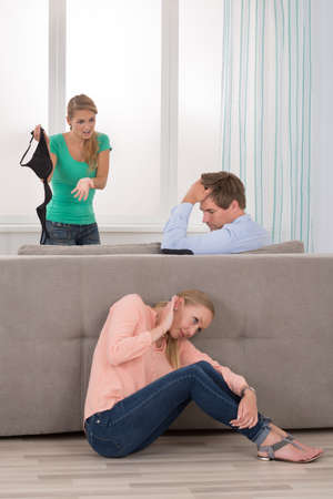 betray: Wife Holding Bra Arguing With Her Husband While His Girlfriend Hiding Behind Sofa Stock Photo