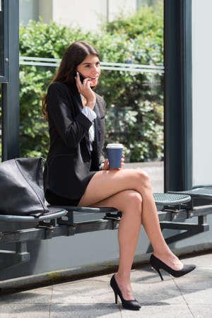 persona sentada: Eliminación joven Empresaria que sostiene el teléfono móvil que habla en la Copa