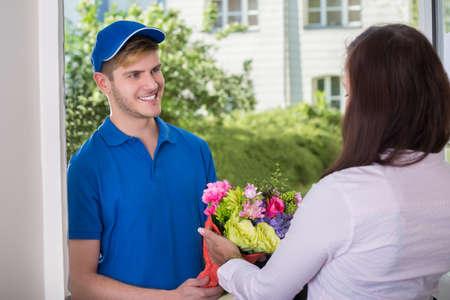 Sonrisa de la mujer joven que recibe el ramo de flores de entrega hombre en el hogar