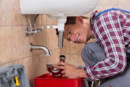 Feliz masculino joven fontanero Instalación de tuberías del fregadero en cuarto de baño