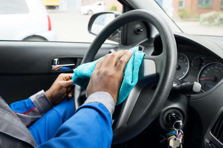 car wheel: Close-up Of A Male Worker Cleaning Car Steering Wheel With Cloth
