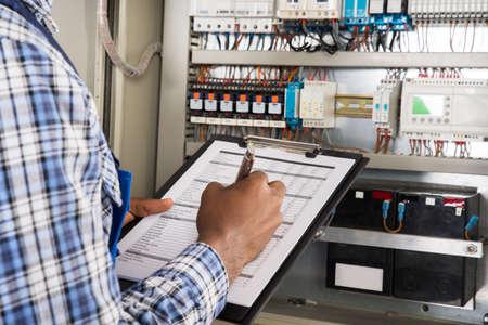 Close-up der männlichen Techniker in Zwischenablage zu schreiben Vor Fusebox