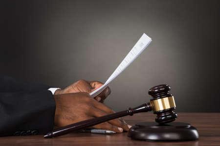 Primer plano De Un Juez De Holding De Papel Con Gavel En Mesa De Madera Foto de archivo