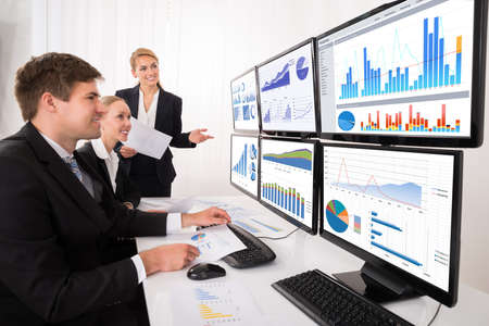 business chart: Young Male And Female Businesspeople Looking At Financial Graphs On Multiple Computers In Office Stock Photo