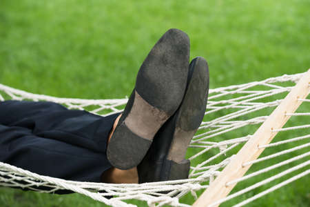 people relaxing: Close-up Of A Man Relaxing In Hammock