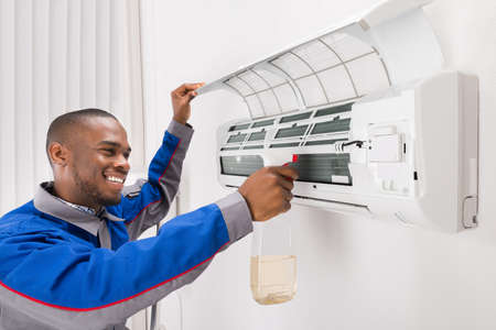 Smiling Male Technician Cleaning Air Conditioner At Home