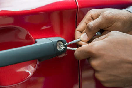 Close-up Of Person Hand Opening Car Door With Lockpicker