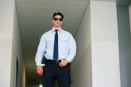 police officer: Young Male Security Guard Standing At The Entrance Stock Photo