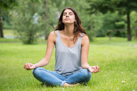 Young Woman Sitting On Green Grass Doing Meditation In Park Stock Photo