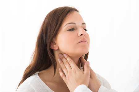 診療所で女性患者の喉に触れる医師の手のクローズ アップ