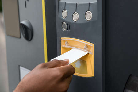 주차를 지불하는 주차 기계에 티켓을 삽입하는 사람의 손 클로즈업 스톡 콘텐츠