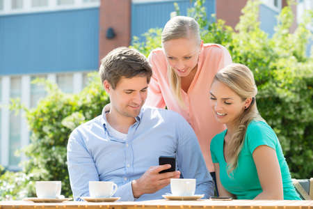 viewing: Group Of Happy Young Friends Looking At Mobile Phone In Cafe Stock Photo