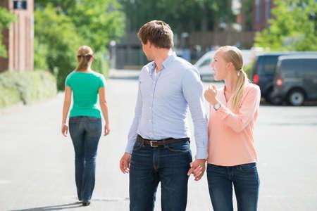 Jeune Crier Femme At Her Boyfriend Regardant l'autre femme sur la rue Banque d'images - 61135071