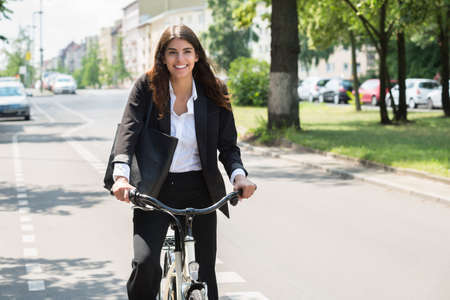 Photo Of Happy Young Businesswoman Commuting On Bicycle Stock Photo