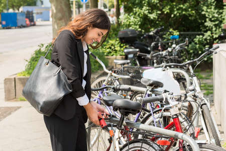 locking up: Smiling Young Businesswoman With Handbag Locking Up Her Bicycle