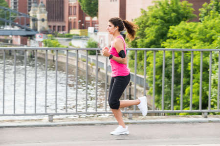 Sporty Young Woman Running On Bridge In Morning Stock Photo