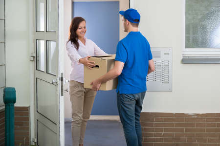 Happy Woman Receiving Package From Delivery Man At The Doorway Archivio Fotografico