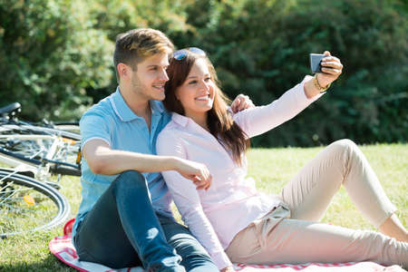 Happy Young Couple Taking Selfie On Smart Phone At Park