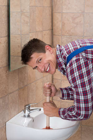 clogged: Smiling Young Male Plumber Using Plunger In Clogged Sink In Bathroom Stock Photo