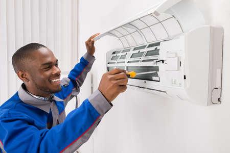 Felice giovane africano maschio tecnico che ripara condizionatore d'aria Archivio Fotografico