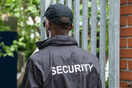 Hintere Ansicht eines männlichen Sicherheitsbeamten, der schwarze Uniform trägt