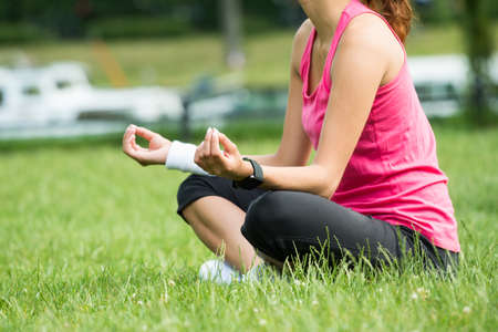Closeup Of Young Woman Sitting On Grass Meditating In Park Stock Photo